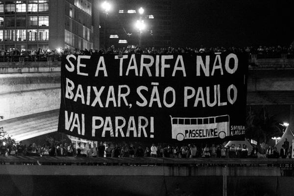 """No dia 6 de junho de 2013 o Movimento Passe Livre bloqueou a Av. 23 de Maio com uma barricada de catracas de papel pegando fogo. Ao fundo, do alto do Viaduto do Chá ao Vale do Anhangabaú, o movimento posicionou uma enorme bandeira com a frase """"SE A TARIFA NÃO BAIXAR SÃO PAULO VAI PARAR"""". À direita estava o prédio da prefeitura de São Paulo. No dia seguinte esta cena foi capa do jornal Folha de S. Paulo, em uma imagem do fotógrafo Nelson Antoine. Aqui estamos publicando outra imagem, de autoria desconhecida, que mostra o bandeirão. (Graziela Kunsch)"""